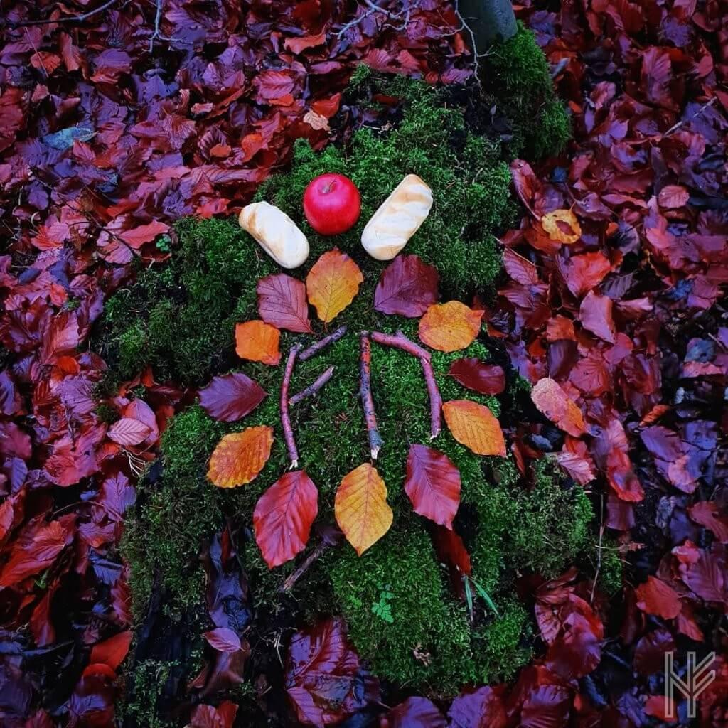 Moosbewachsener Baumstumpf mit Opfergaben, Blättern und Runen